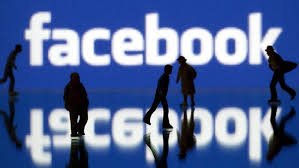 People milling in front of a Facebook sign