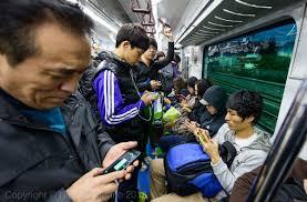 people on phone on train